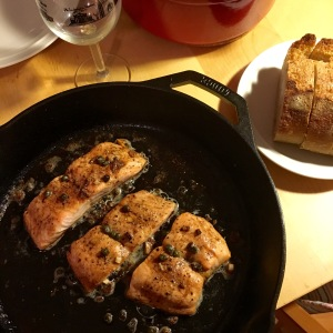 Salmon cooked in anchovy butter with capers; served in a cast iron skillet