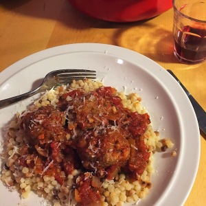 Lamb meatballs with tomato sauce and Israeli couscous. Served with red wine